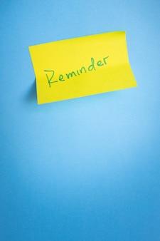 ブルーライトの背景に黄色の粘着メモを思い出させるミニマリストのコンセプト