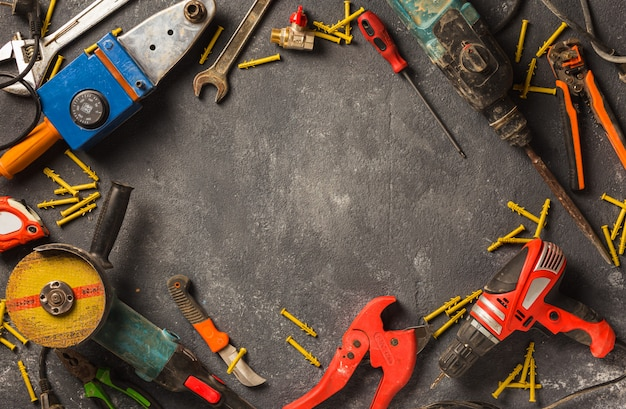 Remodel concept. frame of construction work tools on a dark background top view