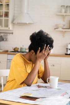 疲れているリモートアフリカのマネージャーまたはフリーランスの建築家は、在宅勤務中に問題の過負荷を抱えています