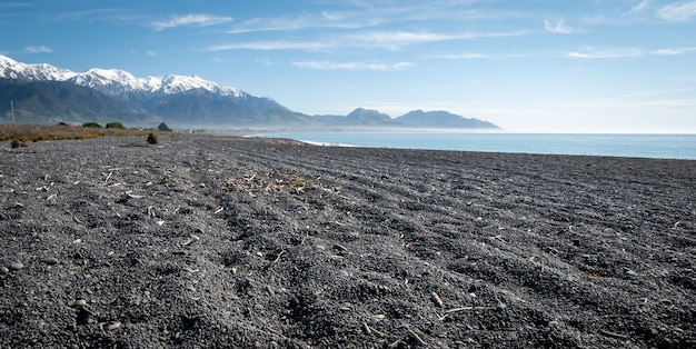 黒い砂利の紺碧の海と青い空と山々のある人里離れたビーチkaikouranewzealand