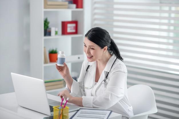 リモート相談。ノートパソコンの前に座って、笑みを浮かべて話している薬を手に白いコートを着た美しい女性。