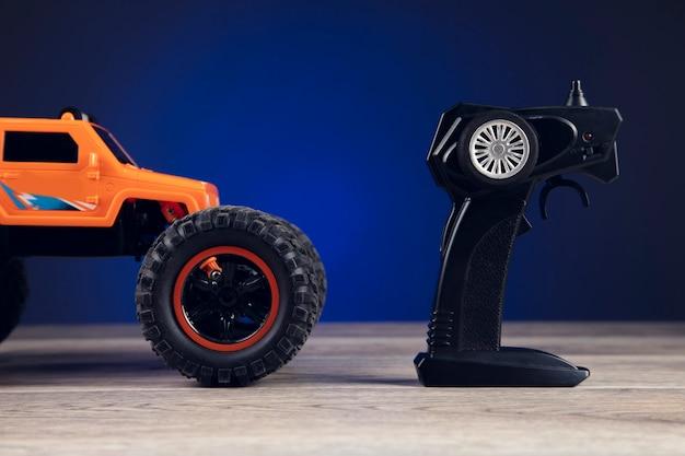 Пульт дистанционного управления и игрушечная машинка на синем