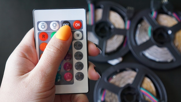 Remote control for change colors in hand on blurred background with led light