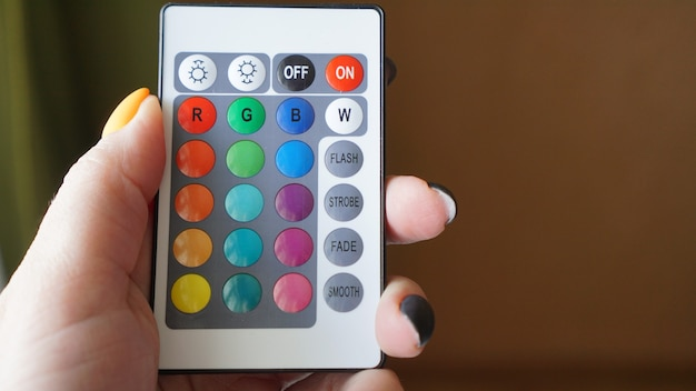 Remote control for change colors in hand on blurred background