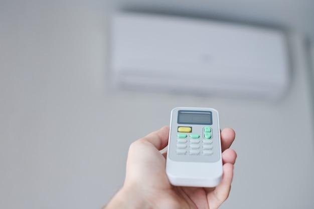 Пульт дистанционного управления кондиционером в руке. дистанционное управление состоянием помещения. реле температуры воздуха для охлаждения помещения.