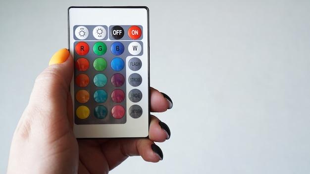Пульт дистанционного управления для изменения цвета в руке, изолированные на белом фоне
