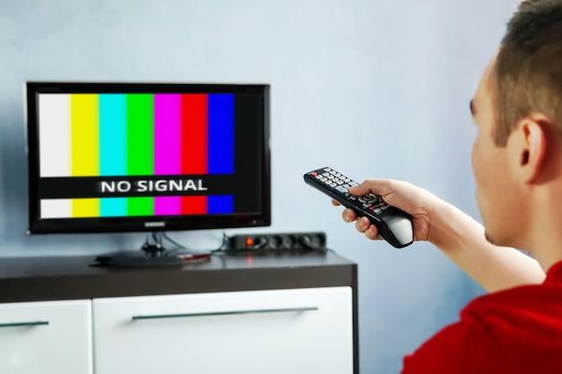 Пульт дистанционного управления в руке перед телевизором. лежебока. нет баннера на экране сигнала