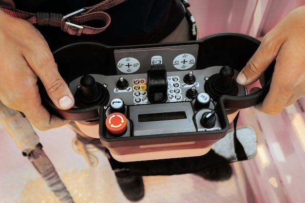 사람의 손에 리프팅 자동차 크레인의 원격 제어. 크레인의 텔레스코픽 버킷을 제어하기위한 조이스틱 및 버튼이있는 패널.