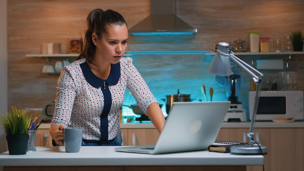 Remote employee working late night at deadline sitting on desk in home kitchen. busy focused businesswoman using modern technology network wireless doing overtime for job reading writing, searching