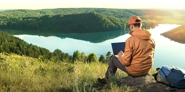 Remote freelancer work in nature.  beautiful view with sunset and lake in background. banner.