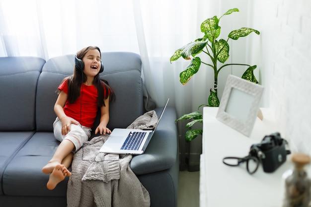 リモートレッスン。子供は幸せそうに笑って、遠隔で知識を得ます。小さな女の子はラップトップで自宅からオンライン学習を勉強します。オンラインスクール。