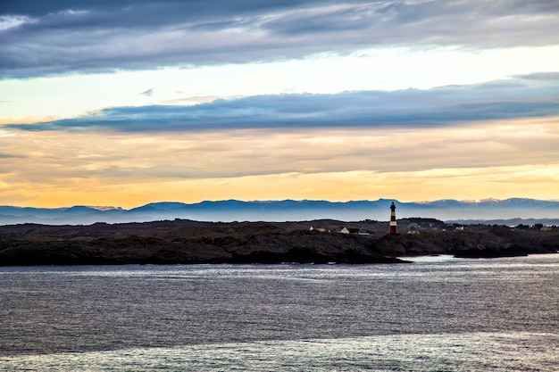 Remote lighthouse and mountains silhouette, norway