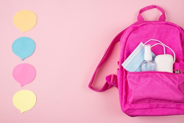 Концепция дистанционного обучения. выражение мнения онлайн концепции. вверху сверху вид сверху фото розового рюкзака, маски, мыла, дезинфицирующего средства для рук и мысленных облаков, изолированных на пастельно-розовом фоне