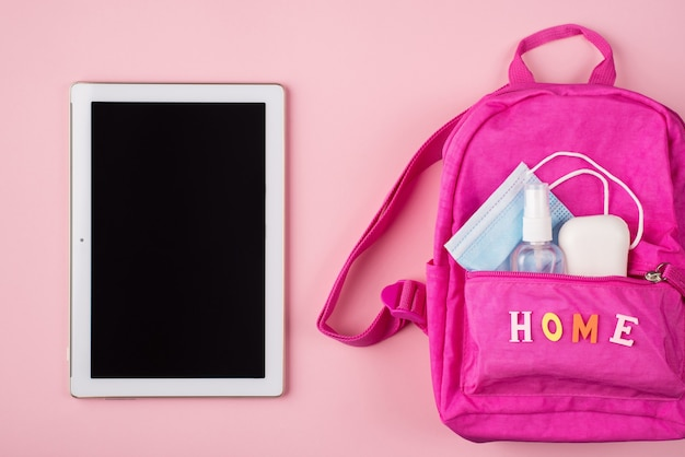 Удаленное обучение и рабочая концепция. вверху вверху фото розового рюкзака, маски, дезинфицирующего мыла, таблетки, изолированной на пастельно-розовом фоне