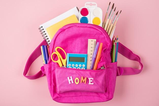 Дистанционное обучение дома концепции. фото розового рюкзака и красочных канцелярских принадлежностей, изолированных на пастельно-розовом фоне, сверху сверху.