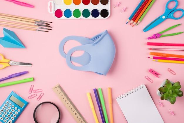 Концепция дистанционного обучения. концепция quarantime. сверху над головой фото синей маски в окружении красочных канцелярских принадлежностей, изолированных на пастельно-розовом фоне