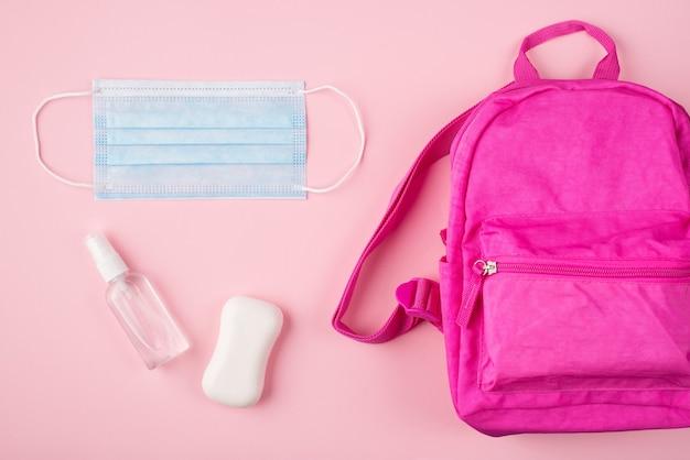 Концепция дистанционного обучения. концепция социального дистанцирования. фото розового рюкзака с синей маской и мылом, дезинфицирующее средство для рук, изолированное на пастельно-розовом фоне