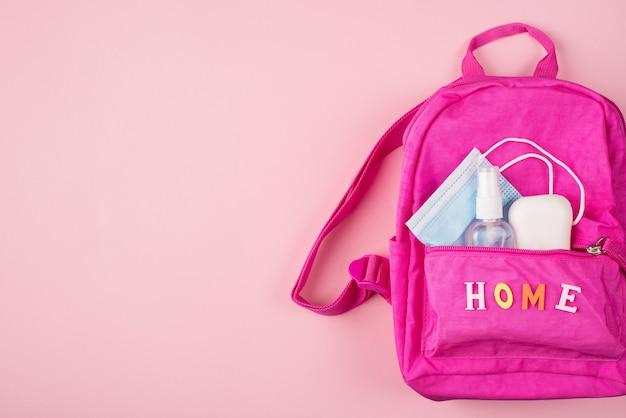 Концепция дистанционного обучения. фото розового рюкзака с синей маской, дезинфицирующее средство для рук, изолированное на пастельно-розовом фоне с copyspace
