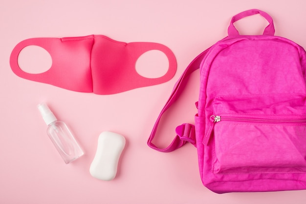 У дистанционного обучения должна быть концепция. концепция карантина. вверху над фото вид розового рюкзака, маска, мыло, дезинфицирующее средство для рук, изолированное на пастельно-розовом фоне