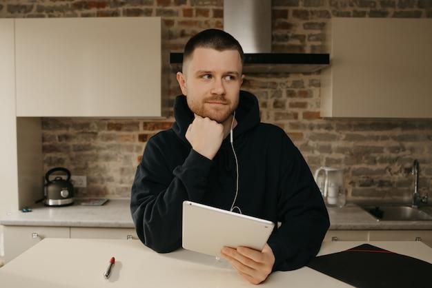 リモート作業。タブレットで遠隔操作するひげを持つ男。ウェビナーを聞くプログラマー。