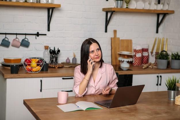 Удаленная работа. женщина разговаривает по телефону, сидя за компьютером на кухне.