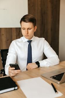 Удаленная работа за компьютером. отвлеченный от работы мужчина смотрит в соцсеть на смартфоне.