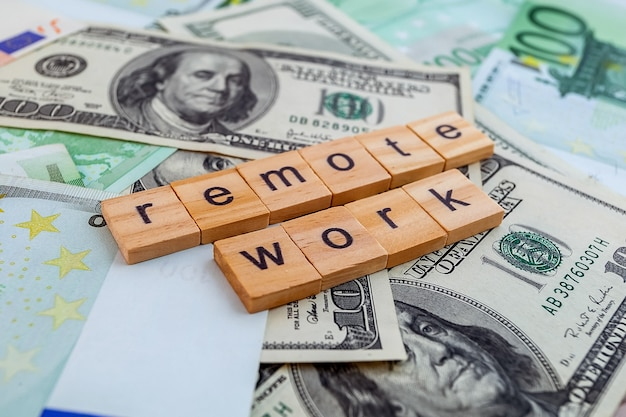 Remote work inscription on wooden cubes on the texture of us dollars and euro banknotes