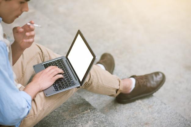 リモートワーク。男性のための現代技術。社会的コミュニケーション。悪い習慣を持つ認識できないビジネスマン、空の白い画面のモックアップとラップトップ