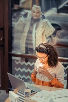 リモートワーク。ノートパソコンに座って仕事をしている素敵なアフリカ系アメリカ人女性