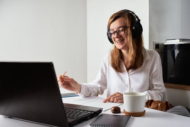 Удаленная работа. онлайн-курс, дистанционное образование и концепция электронного обучения. женщина в наушниках слушает аудиокурс на ноутбуке и делает отметки в записной книжке