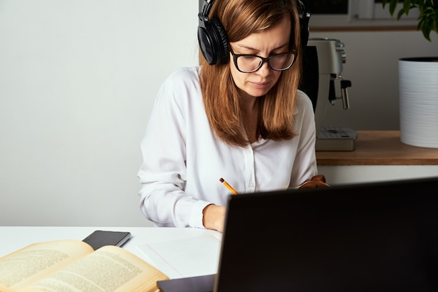 원격 작업. 온라인 코스, 원격 교육 및 e- 러닝 개념. 헤드폰에서 여자 노트북에서 오디오 과정을 듣으십시오