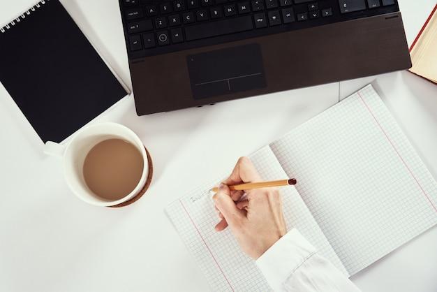 원격 작업. 여자는 노트북에 노트를 만들고 연구를 위해 노트북을 사용합니다. 원격 교육 및 e- 러닝 개념