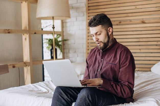 Удаленная работа. молодой человек, работающий на компьютере на дому