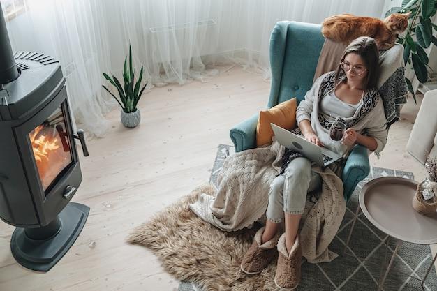 원격 작업. 아늑한 안락의자에서 노트북을 사용하고 집에서 차를 마시며 집에서 고양이와 함께 벽난로 옆에 격자 무늬로 앉아 있는 젊은 여성