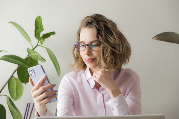 自宅からリモート作業。ノートパソコン、コーヒー、眼鏡のフリーランサー。遠隔教育、分離、女性のビジネス、オンラインショッピングの概念。 Premium写真