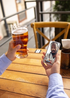 Удаленная работа, онлайн-развлечения во время карантина. человек смотрит поток в баре, ресторане с пк, устройствами и гаджетами. концепция дистанционного обучения, изоляции, бизнеса, покупок, конференции.