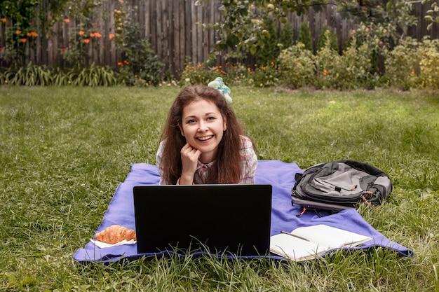 ノートパソコンの前の草の上に横たわって在宅勤務の若い女性