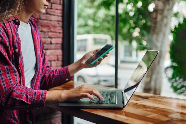 喫茶店の窓際でノートパソコンをリモートでオンラインでスマートに作業。居心地の良い職場