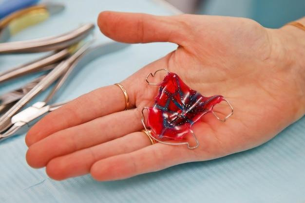 歯科医が医療用テーブルの上に置いた取り外し可能なクラスププロテーゼ。医師のクローズアップの手で歯科補綴物。歯科医は歯科用ブリッジを持っています。入れ歯の補綴のための歯科医院。コピースペース