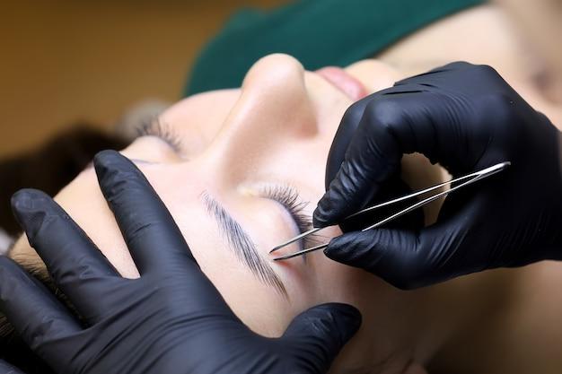 Удаление остатков нежелательных волосков на бровях модели после процедуры ламинирования. мастер держит в руках пинцет, который удаляет волоски