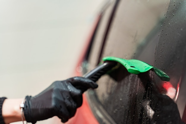 Removal of residual water from the glass with a rubber scraper after washing the car. car wash. self-service complex. high-pressure car wash.