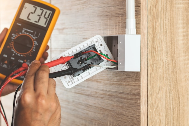 Remove the power electric plug socket from the outlet box on the wooden wall to measure the voltage with a digital meter.
