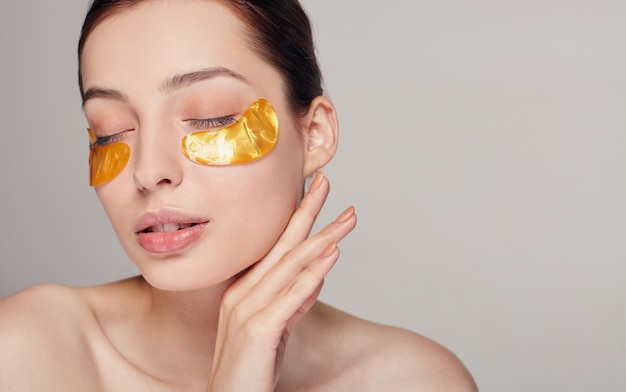 Remove wrinkles and dark circles. a woman takes care of delicate skin around her eyes. cosmetic procedures. fresh facial skin.