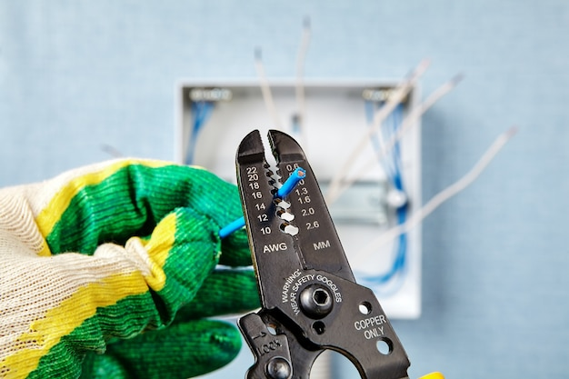 Удаляет изоляцию с конца медного провода, используя инструмент для снятия изоляции.