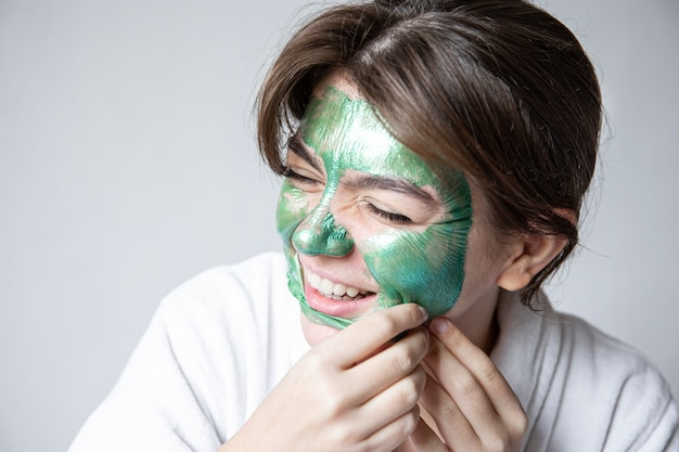 Removing a green cosmetic mask from the attractive girl face