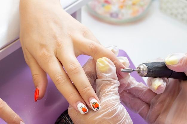 Удаление шеллака. аппаратный маникюр. мастер маникюра производит шлифовку ногтевой пластины клиенту маникюрным аппаратом
