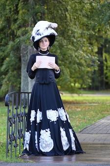 Женщина эпохи возрождения с книгой на мосту в парке