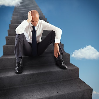 Rendering thoughtful businessman sitting on the steps of an infinite scale