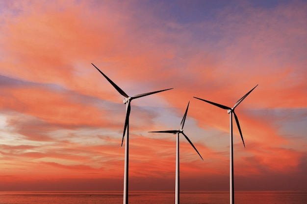 Renewable alternative energy produced by wind turbines on a background of red sunset cloudy sky above wide sea with copy space. ecological alternative energy concept.