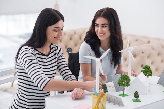 Возобновляемая энергия. веселая женщина с ограниченными возможностями и коллега улыбается и работает с моделями альтернативной энергии